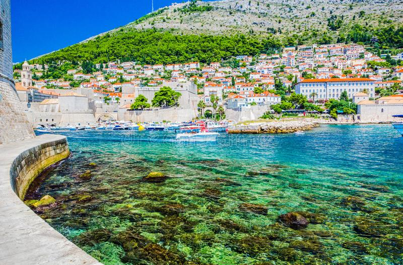 Panorama da cidade velha de Dubrovnik na Croácia, lote dos barcos na água azul imagens de stock royalty free