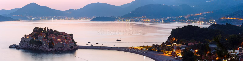 Panorama da ilhota do mar do por do sol e do Sveti Stefan (Montenegro) fotografia de stock