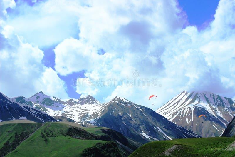 Panorama da montanha com paragliders Picos cênicos de céu azul e de montanha na neve fotos de stock royalty free