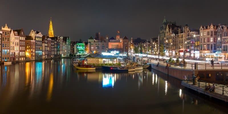 Panorama da noite do canal Damrak de Amsterdão, Holanda imagem de stock