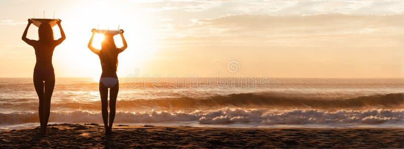Panorama da praia do por do sol dos surfistas & das prancha das mulheres do biquini fotos de stock royalty free