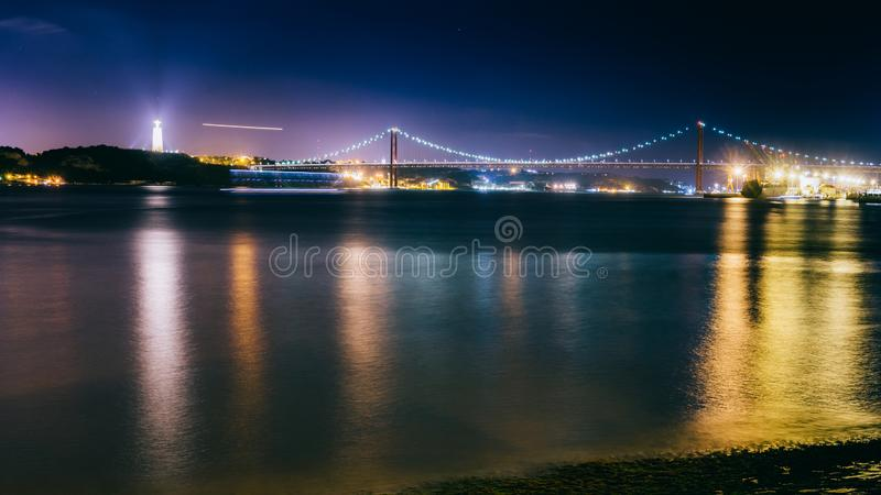 Panorama de 25ème April Bridge à Lisbonne, Portugal croisant le Tage la nuit Dessus laissé est le Cristo Rei Statue photo libre de droits
