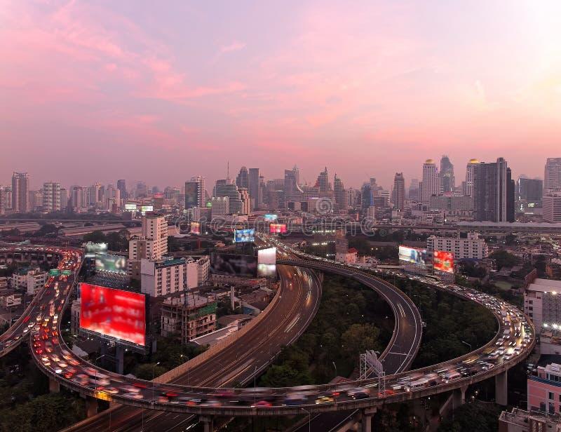 Panorama de Bangkok en la oscuridad con los rascacielos en fondo y la circulación densa en las autopistas elevadas y los intercam imagen de archivo