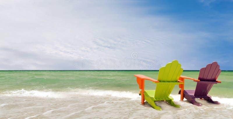 Panorama de cadeiras coloridas em uma praia tropical fotos de stock