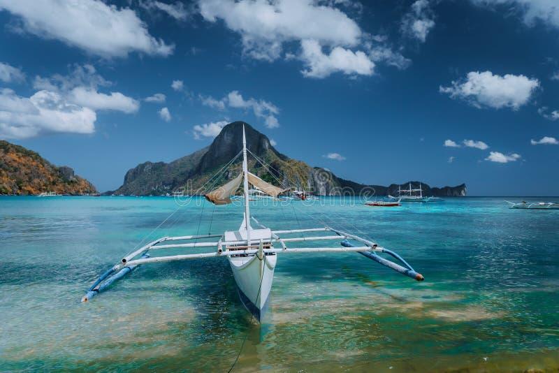 Panorama de Cadlao avec le bateau traditionnel de banca de filippino dans l'avant Baie tropicale exotique d'EL Nido, île de Palaw image libre de droits