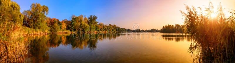 Panorama de coucher du soleil de lac dans l'or et le bleu photographie stock