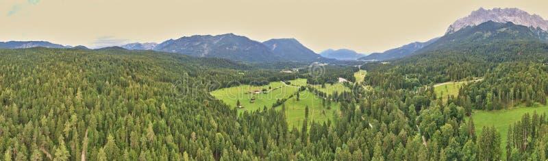 Panorama de floresta e vale com prados e pastagens em frente às montanhas dos Alpes, composto por várias antenas foto de stock