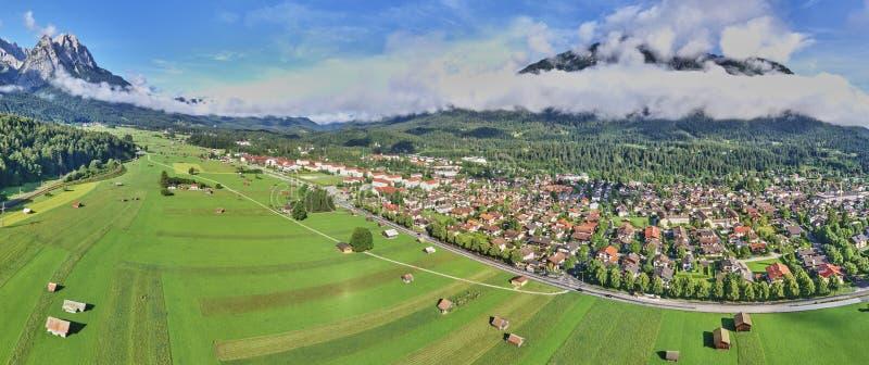 Panorama de fotos aéreas compostas de uma casa de férias atrás de um campo com celeiros e galpões em frente à enorme casa imagem de stock