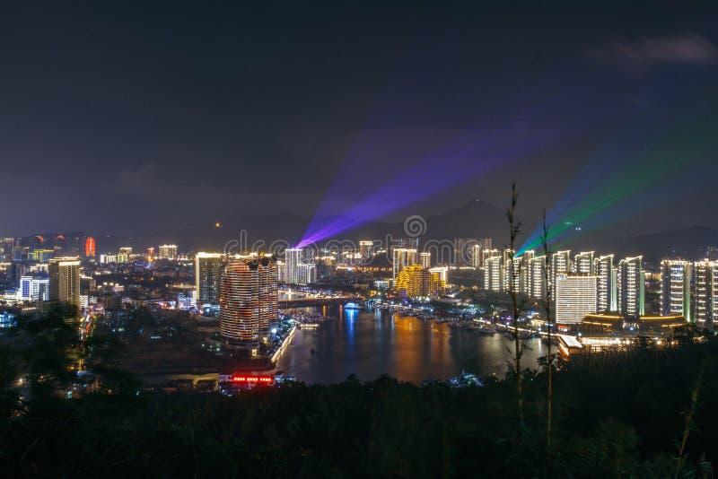 Panorama de la ciudad, del mar y de los edificios de la noche del centro turístico isleño Sanya de Phoenix de los hoteles imágenes de archivo libres de regalías