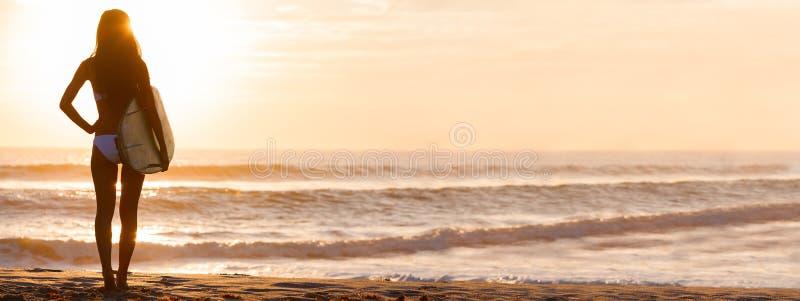 Panorama de la playa de la puesta del sol de la persona que practica surf y de la tabla hawaiana del bikini de la mujer fotografía de archivo