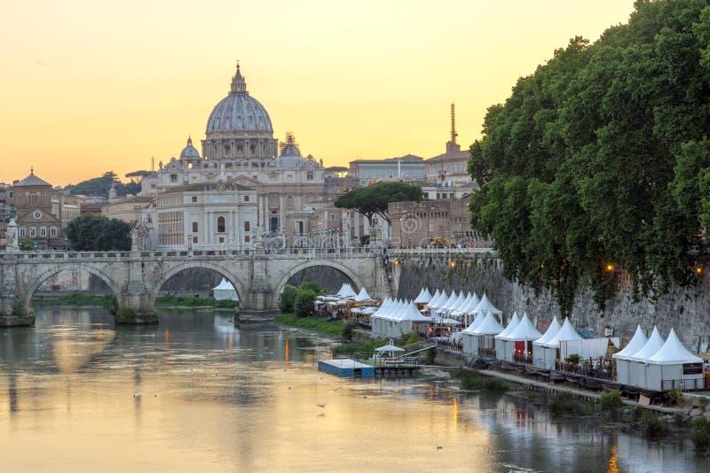 Panorama de la puesta del sol del río de Tíber, de St Angelo Bridge y de la basílica de San Pedro en Roma, Italia fotos de archivo