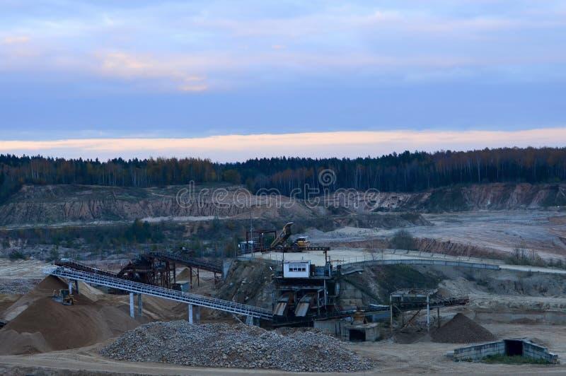 Panorama de la visión superior de la mina de tira profunda del caolín con los camiones y las grúas de descargador Mina para la ex fotos de archivo libres de regalías