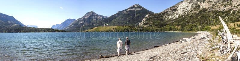 Panorama de lac se tenant prêt de père et de fils avec des montagnes à l'arrière-plan images stock