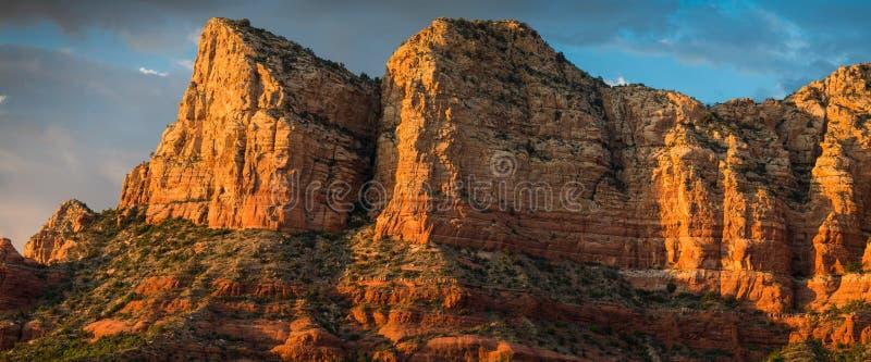 Panorama de las formaciones y de los picos rojos de roca de la piedra arenisca hermosa en la hora de oro debajo de un cielo dramá imágenes de archivo libres de regalías