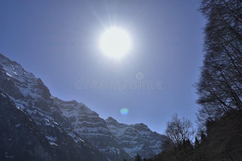 Panorama de los Alpes bajo el sol directo en el cielo azul cerca del lago Klöntalersee imagenes de archivo