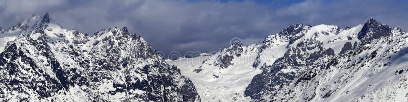 Panorama de montanhas nevados com a geleira em nuvens de tempestade no inverno foto de stock royalty free