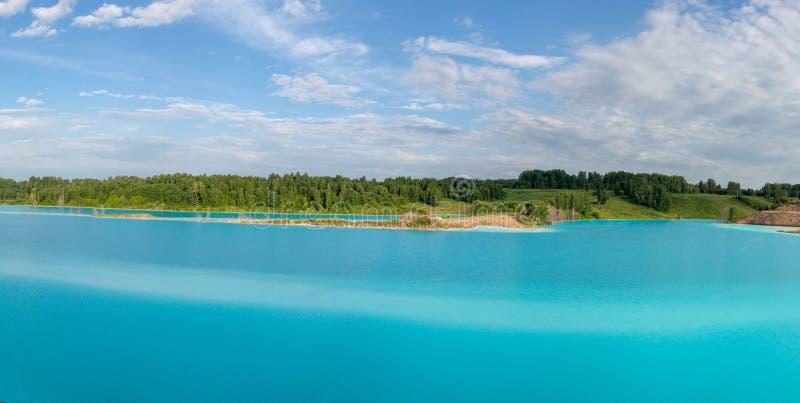 Panorama de um lago bonito com água azul celeste-azul ?rvores verdes, c?u azul com nuvens brancas fotos de stock royalty free