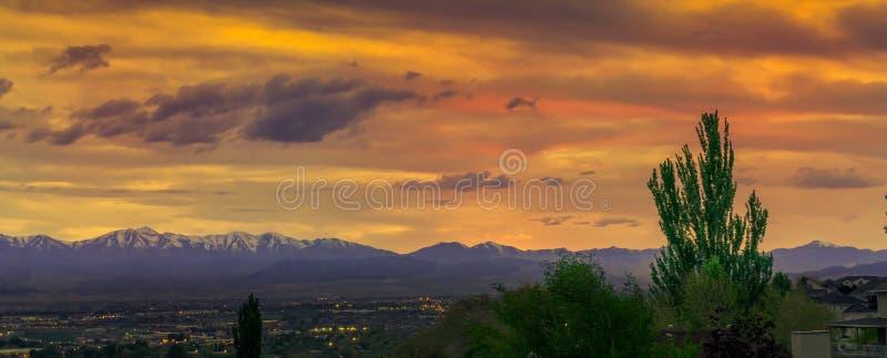 Panorama de um vale com as luzes e as montanhas da cidade no fundo sob um por do sol impressionante fotografia de stock