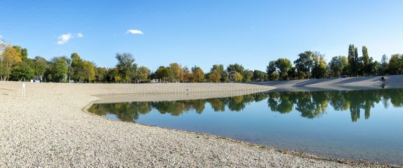 Panorama de uma praia de seixo num lago no Parque Municipal de Bundek, Zagreb, Croácia imagem de stock royalty free