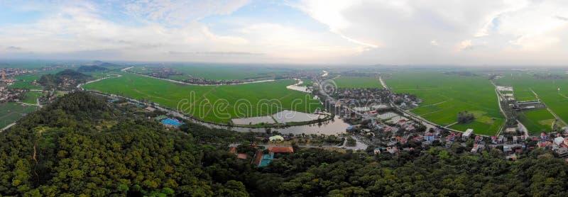 Panorama de un pequeño pueblo entre campos verdes del arroz imagen de archivo