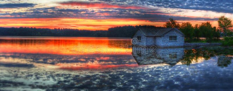 Panorama de una salida del sol en un lago fotos de archivo