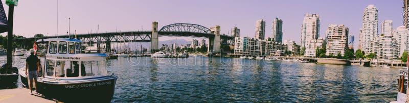 Panorama de Vancouver False Creek au coucher du soleil avec le pont et le bateau photographie stock libre de droits