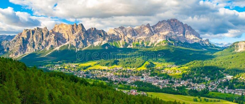 Panorama del ` Ampezzo della cortina d con i prati verdi ed i picchi alpini sui precedenti Dolomia, Italia fotografia stock libera da diritti