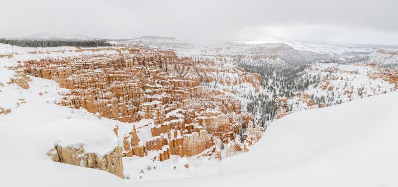 Panorama del canyon di Bryce con neve in inverno con le rocce ed il cielo blu rossi fotografia stock