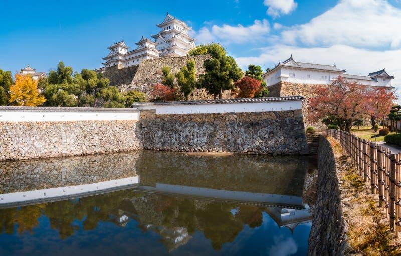 Panorama del castello di Himeji in autunno con le riflessioni nello stagno alla base delle sue pareti di pietra immagini stock