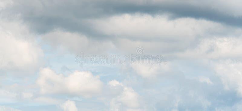 Panorama del cielo tempestoso con le nuvole in varie tonalità di grigio con un suggerimento di cielo blu fotografia stock libera da diritti