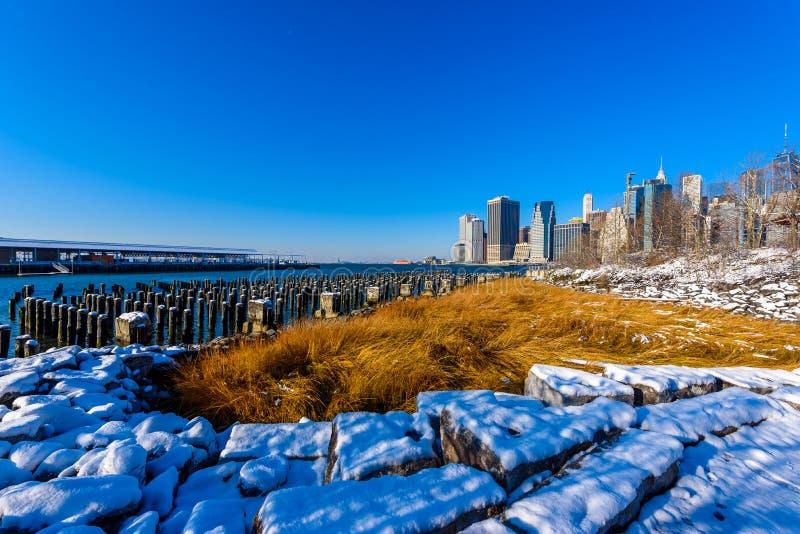Panorama del horizonte del Lower Manhattan en invierno nevoso del riverbank del parque del puente de Brooklyn, New York City, los foto de archivo libre de regalías