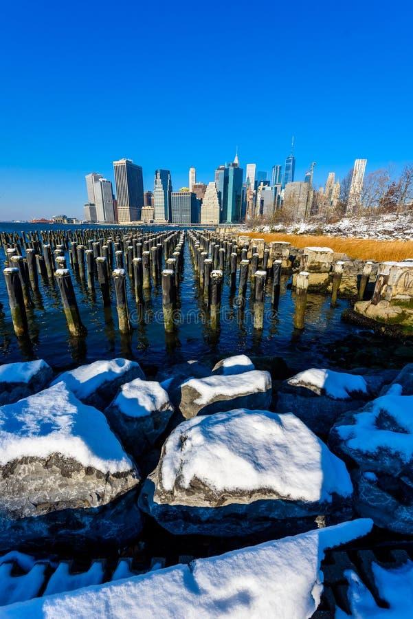 Panorama del horizonte del Lower Manhattan en invierno nevoso del riverbank del parque del puente de Brooklyn, New York City, los imagen de archivo libre de regalías