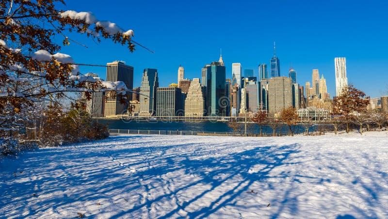 Panorama del horizonte del Lower Manhattan en invierno nevoso del riverbank del parque del puente de Brooklyn, New York City, los fotos de archivo libres de regalías