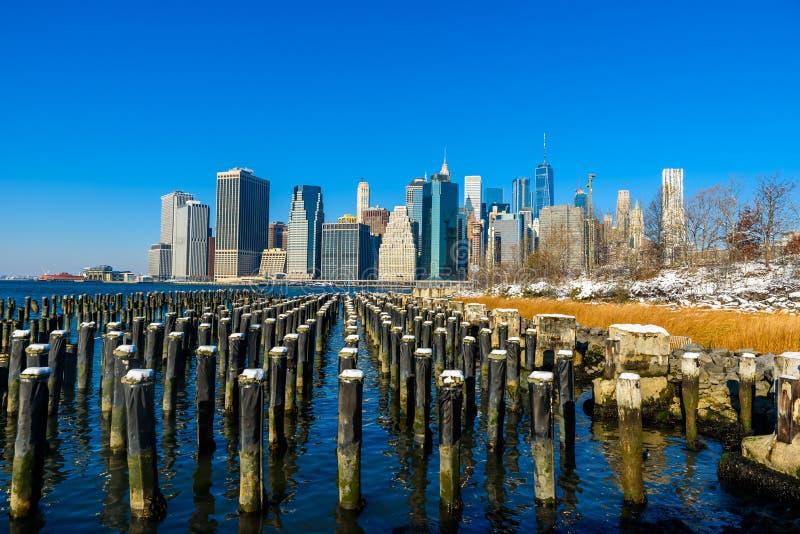 Panorama del horizonte del Lower Manhattan en invierno nevoso del riverbank del parque del puente de Brooklyn, New York City, los fotografía de archivo