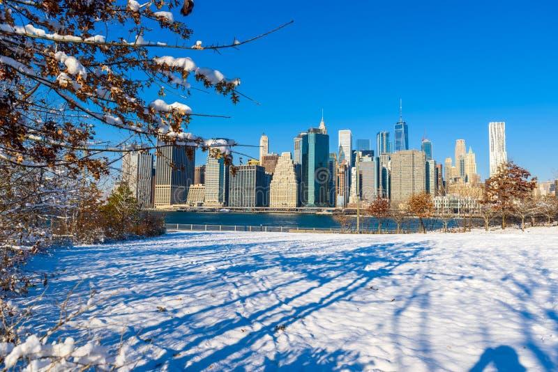 Panorama del horizonte del Lower Manhattan en invierno nevoso del riverbank del parque del puente de Brooklyn, New York City, los imágenes de archivo libres de regalías