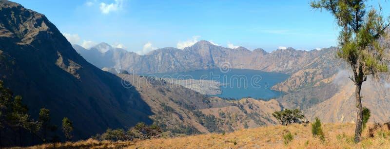 Panorama del lago nel cratere del vulcano Rinjani, una piccola eruzione, isola di Lombok, Indonesia immagine stock