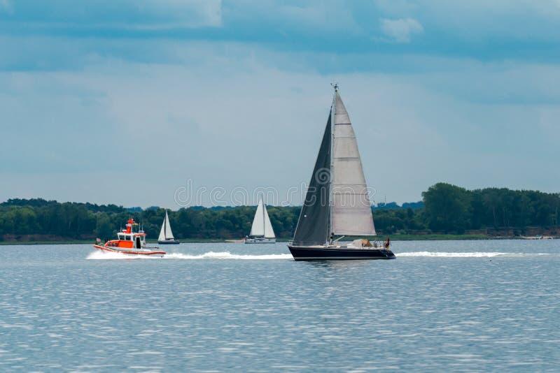 Panorama del mar con tres barcos de navegación y un bote salvavidas imagen de archivo libre de regalías