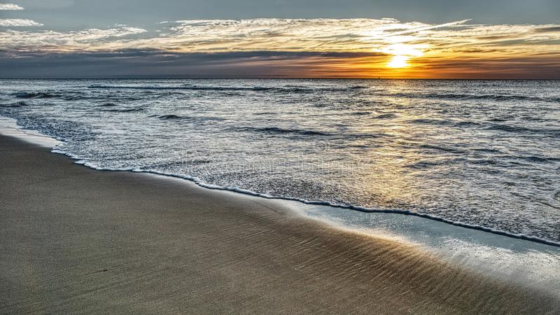Panorama del paisaje marino de la puesta del sol del mar con las ondas y las nubes suaves imagen de archivo libre de regalías