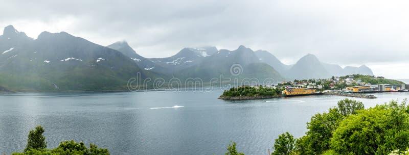 Panorama del pueblo de la isla de Husoy con las montañas en el fondo, isla de Senja, condado de Troms, Noruega fotografía de archivo libre de regalías