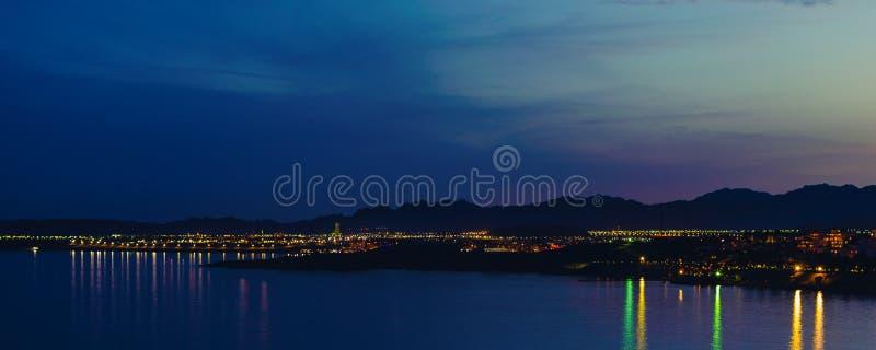 Panorama del Sharm el Sheikh de la noche contra el contexto de las montañas y la reflexión de linternas en el mar fotografía de archivo