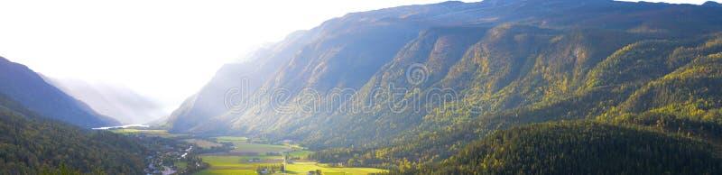 Panorama del valle con las montañas y los rayos solares revestidos del bosque foto de archivo libre de regalías