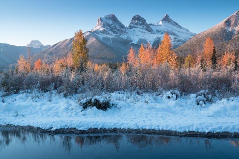 Panorama dell'alba autunnale sulla montagna delle Tre Sorelle con alberi colorati Canmore, Alberta con riflesso in acqua calma immagine stock libera da diritti