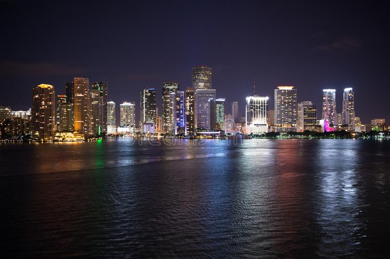Panorama dell'orizzonte della città di Miami alla notte, S.U.A. L'illuminazione dei grattacieli riflette sull'acqua di mare nel c fotografia stock libera da diritti