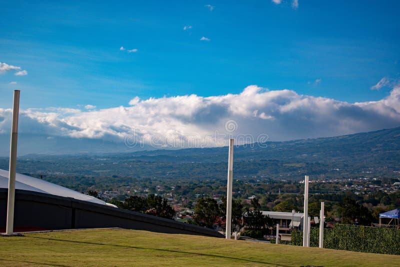 Panorama della città con le montagne ed il cielo immagini stock