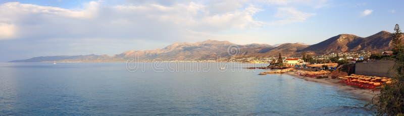 Panorama della città di Hersonissos con la sera con un'incandescenza morbida di tramonto Creta, in Grecia e montagne immagini stock libere da diritti