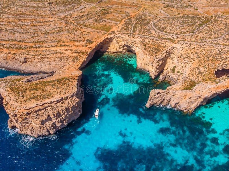 Panorama della laguna blu Comino Malta Cote Azur, acqua della radura del turchese con la sabbia bianca Siluetta dell'uomo Cowerin fotografia stock libera da diritti