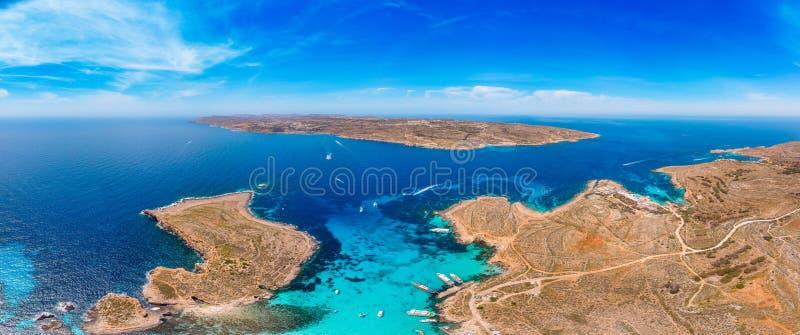 Panorama della laguna blu Comino Malta Cote Azur, acqua della radura del turchese con la sabbia bianca Siluetta dell'uomo Cowerin immagine stock libera da diritti