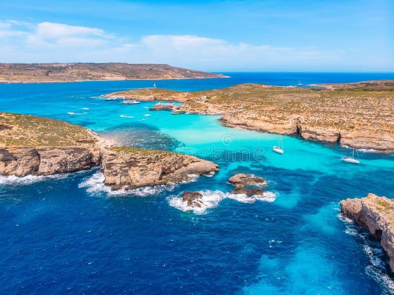 Panorama della laguna blu Comino Malta Cote Azur, acqua della radura del turchese con la sabbia bianca Siluetta dell'uomo Cowerin fotografia stock