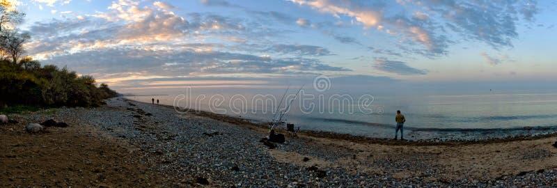 Panorama della spiaggia al Mar Baltico vicino a Khlungsborn/Kuehlungsborn in Germania con il pescatore e le nuvole epiche durante immagine stock libera da diritti