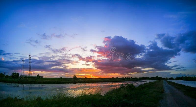 Panorama der Teich reflektiert das Licht von der orange Sonne Der Poolrand ist grünes und gelbes Gras Der Glättungshimmel vor stockbild
